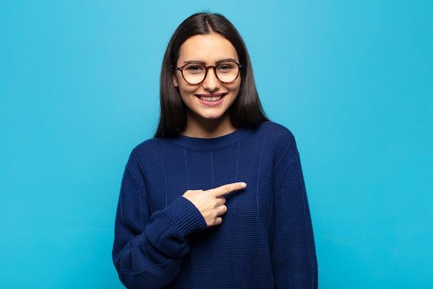 Jovem hispânica parecendo orgulhosa, confiante e feliz, sorrindo e apontando para si mesma ou fazendo o primeiro sinal