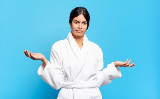 Jovem hispânica parecendo perplexa, confusa e estressada, pensando entre as diferentes opções, sentindo-se insegura conceito de roupão de banho