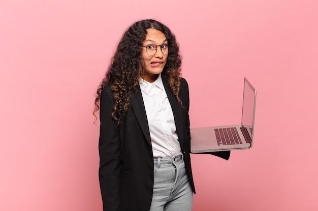 Jovem hispânica parecendo perplexa e confusa, mordendo o lábio com um gesto nervoso, sem saber a resposta para o problema. computador portátil