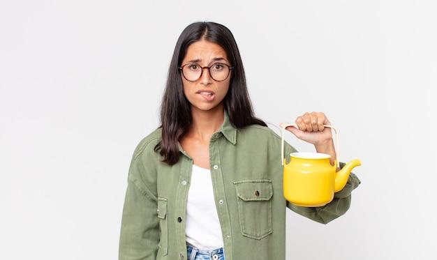 Jovem hispânica parecendo perplexa e confusa, segurando um bule de chá Foto Premium