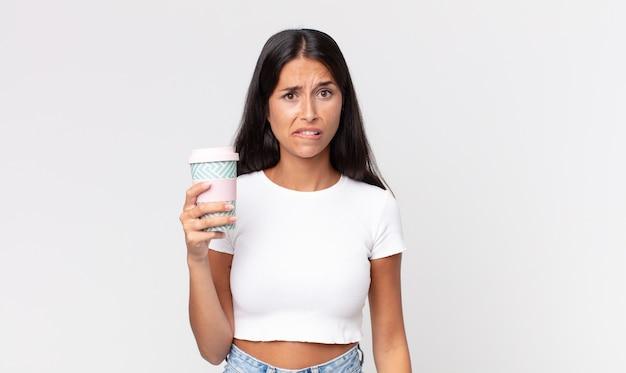 Jovem hispânica parecendo perplexa e confusa, segurando uma embalagem de café para viagem Foto Premium