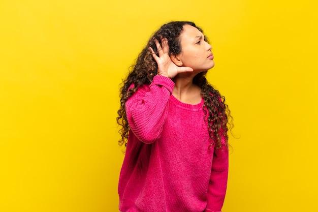 Jovem hispânica parecendo séria e curiosa, ouvindo, tentando ouvir uma conversa secreta ou fofoca, espionando