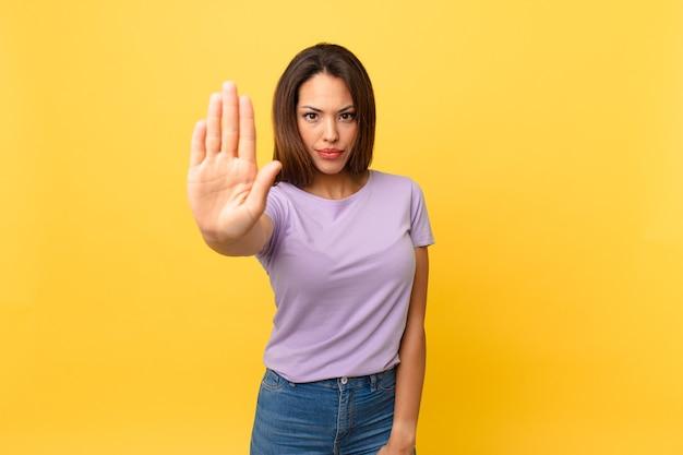 Jovem hispânica parecendo séria, mostrando a palma da mão aberta fazendo gesto de pare