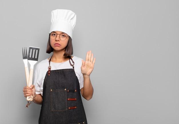 Jovem hispânica parecendo séria, severa, descontente e irritada, mostrando a palma da mão aberta fazendo gesto de pare