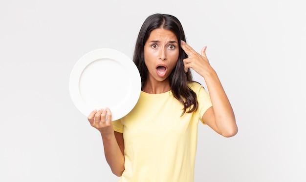 Jovem hispânica parecendo surpresa, percebendo um novo pensamento, ideia ou conceito e segurando um prato vazio