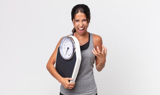 Jovem hispânica parecendo zangada, irritada e frustrada e segurando uma balança. conceito de dieta
