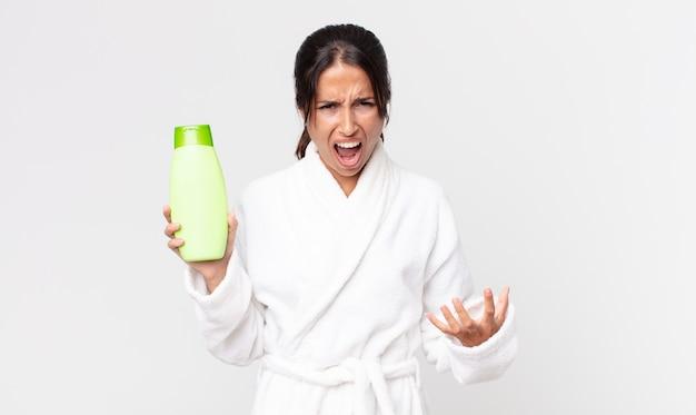 Jovem hispânica parecendo zangada, irritada e frustrada, vestindo um roupão de banho e segurando um shampoo