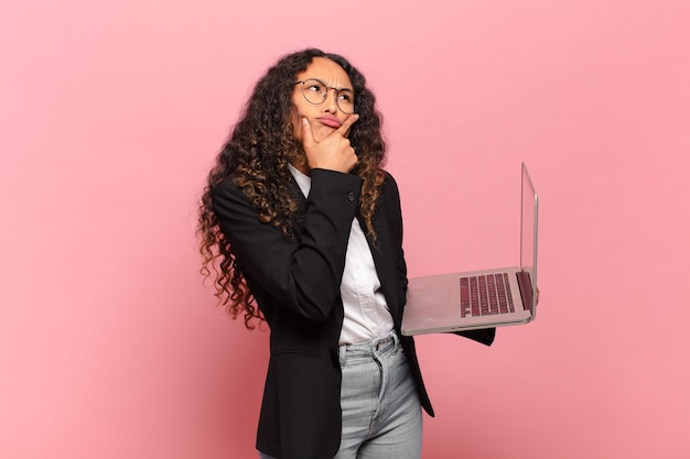 Jovem hispânica pensando, sentindo-se duvidosa e confusa, com diferentes opções, se perguntando qual decisão tomar. conceito de laptop