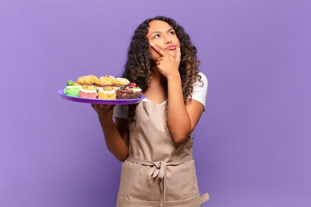 Jovem hispânica pensando, sentindo-se duvidosa e confusa, com diferentes opções, se perguntando qual decisão tomar. cozinhar bolos conceito