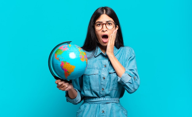 Jovem hispânica se sentindo chocada e com medo segurando um globo terrestre