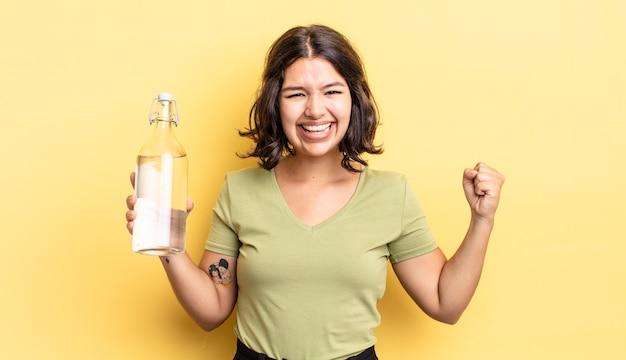 Jovem hispânica se sentindo chocada, rindo e comemorando o sucesso. conceito de garrafa de água