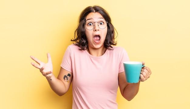 Jovem hispânica se sentindo extremamente chocada e surpresa. conceito de caneca de café