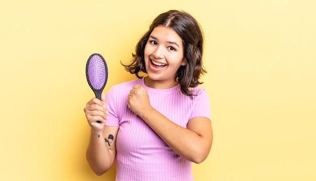 Jovem hispânica se sentindo feliz e enfrentando um desafio ou comemorando. conceito de escova de cabelo