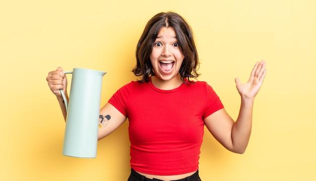 Jovem hispânica se sentindo feliz e surpresa com algo inacreditável. conceito de garrafa térmica