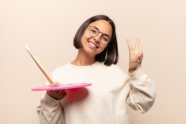 Jovem hispânica se sentindo feliz, maravilhada, satisfeita e surpresa, mostrando gestos de ok e polegar para cima, sorrindo