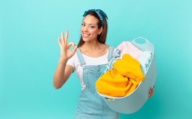 Jovem hispânica se sentindo feliz, mostrando aprovação com gesto de ok e lavando roupa