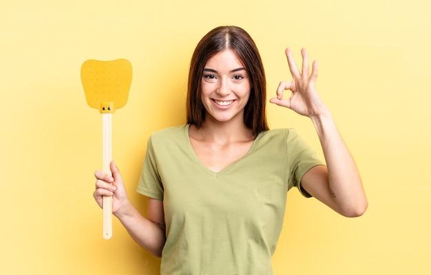 Jovem hispânica se sentindo feliz, mostrando aprovação com um gesto certo. conceito de matar moscas