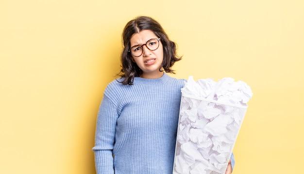 Jovem hispânica se sentindo intrigada e confusa com o conceito de lixo