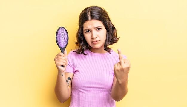 Jovem hispânica se sentindo irritada, irritada, rebelde e agressiva. conceito de escova de cabelo