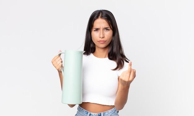 Jovem hispânica se sentindo irritada, irritada, rebelde e agressiva segurando uma garrafa térmica de café