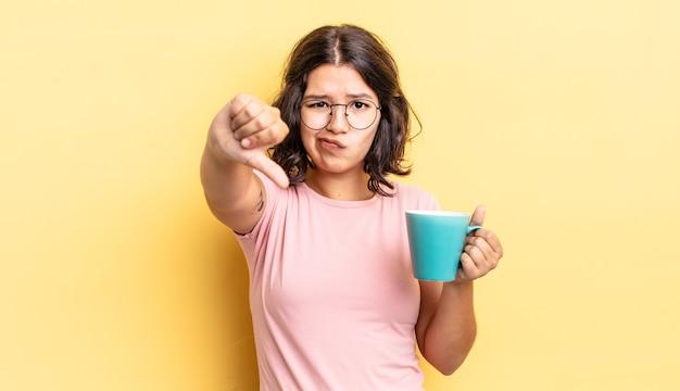 Jovem hispânica se sentindo mal, mostrando os polegares para baixo. conceito de caneca de café