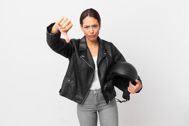 Jovem hispânica se sentindo mal, mostrando os polegares para baixo. conceito de motociclista