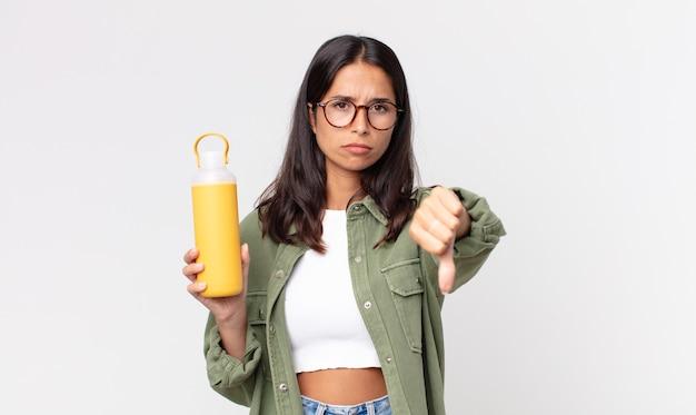 Jovem hispânica se sentindo mal, mostrando os polegares para baixo e segurando uma garrafa térmica de café