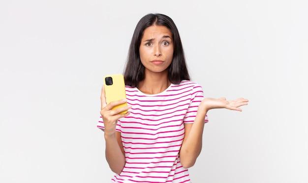Jovem hispânica se sentindo perplexa e confusa, duvidando e segurando um smartphone