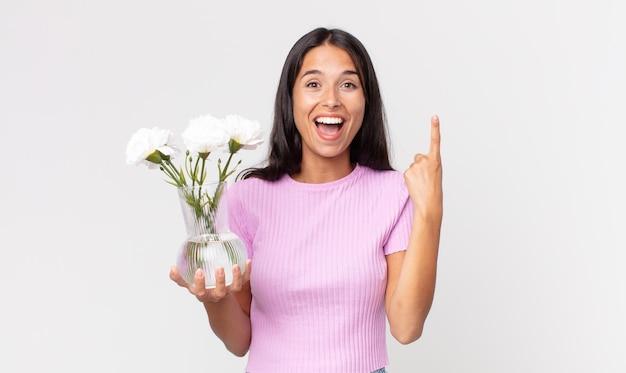 Jovem hispânica se sentindo um gênio feliz e animado após ter uma ideia segurando flores decorativas