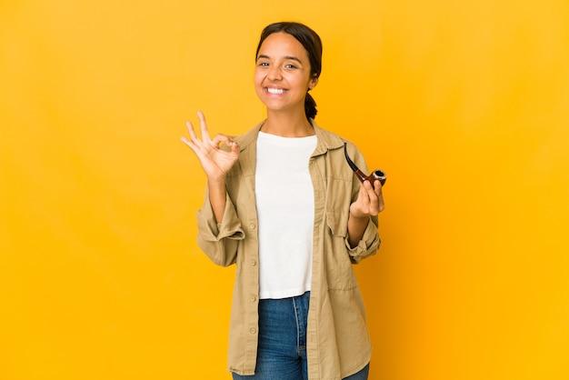Jovem hispânica segurando um cachimbo, alegre e confiante, mostrando um gesto de ok