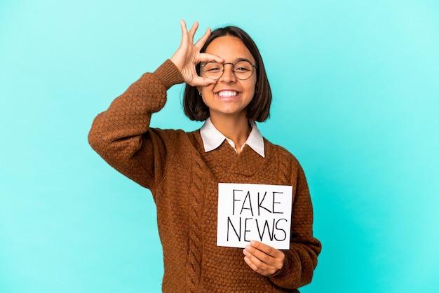 Jovem hispânica segurando um cartaz de notícias falsas animada com um gesto de ok nos olhos