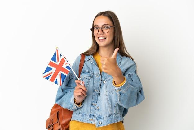 Jovem hispânica segurando uma bandeira do reino unido sobre um fundo branco isolado com o polegar para cima porque algo de bom aconteceu