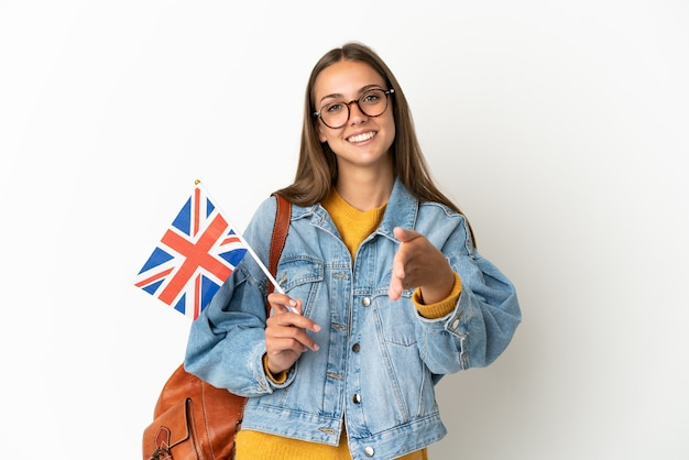 Jovem hispânica segurando uma bandeira do reino unido sobre um fundo branco isolado, cumprimentando-se para fechar um bom negócio