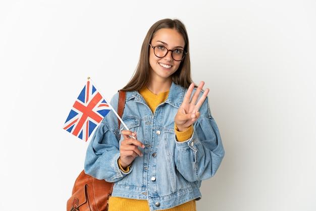Jovem hispânica segurando uma bandeira do reino unido sobre um fundo branco isolado feliz e contando três com os dedos