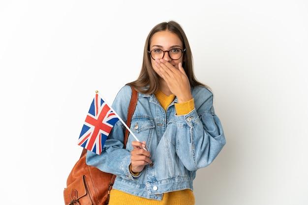 Jovem hispânica segurando uma bandeira do reino unido sobre um fundo branco isolado, feliz e sorridente, cobrindo a boca com a mão