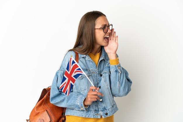 Jovem hispânica segurando uma bandeira do reino unido sobre um fundo branco isolado, gritando com a boca aberta para o lado