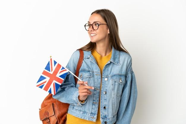 Jovem hispânica segurando uma bandeira do reino unido sobre um fundo branco isolado, olhando para o lado e sorrindo