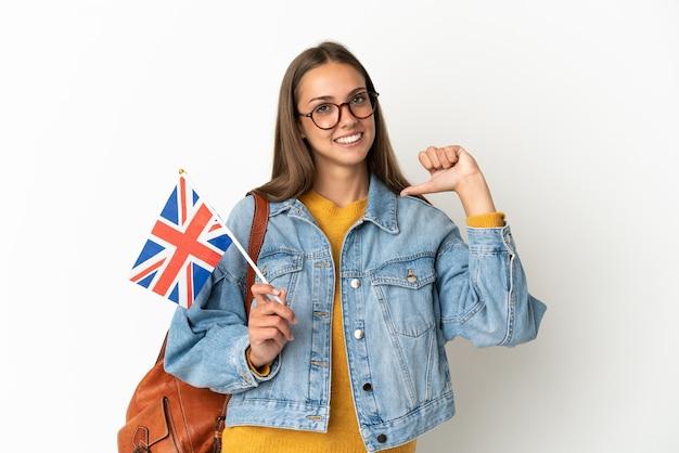Jovem hispânica segurando uma bandeira do reino unido sobre um fundo branco isolado, orgulhosa e satisfeita