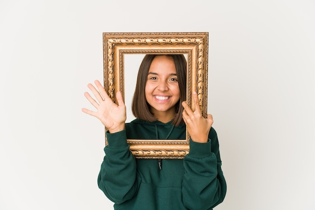 Jovem hispânica segurando uma velha moldura sorrindo alegre mostrando o número cinco com os dedos