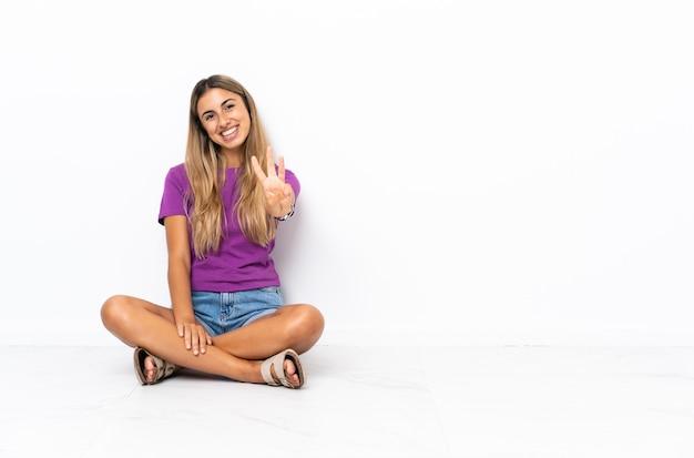 Jovem hispânica sentada feliz no chão contando três com os dedos