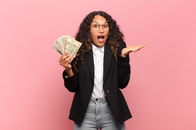 Jovem hispânica sentindo-se extremamente chocada e surpresa, ansiosa e em pânico, com um olhar estressado e horrorizado. conceito de notas de dólar