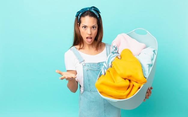 Jovem hispânica sentindo-se extremamente chocada e surpresa, lavando roupas