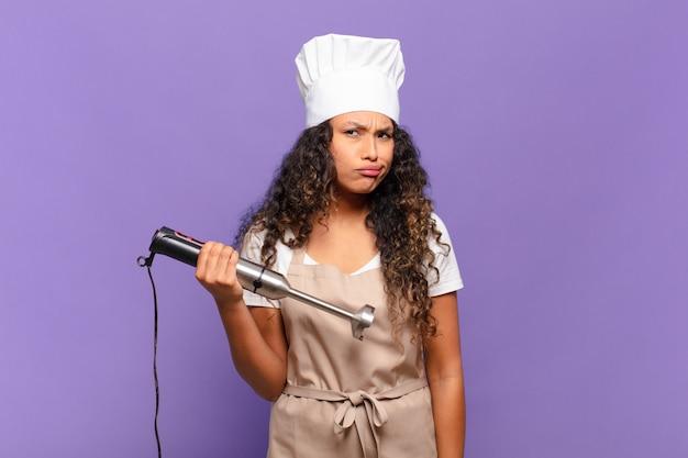 Jovem hispânica sentindo-se perplexa e confusa, com uma expressão muda e atordoada olhando para algo inesperado. conceito de chef