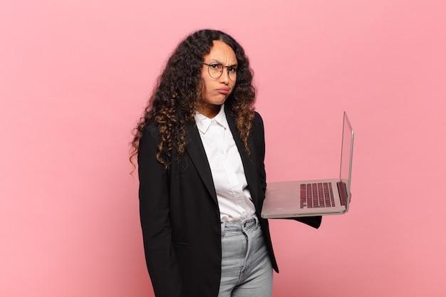 Jovem hispânica sentindo-se perplexa e confusa, com uma expressão muda e atordoada olhando para algo inesperado. conceito de laptop