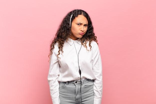 Jovem hispânica sentindo-se perplexa e confusa, com uma expressão muda e atordoada olhando para algo inesperado. conceito de telemarketing