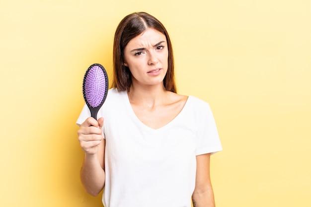 Jovem hispânica sentindo-se perplexa e confusa. conceito de escova de cabelo