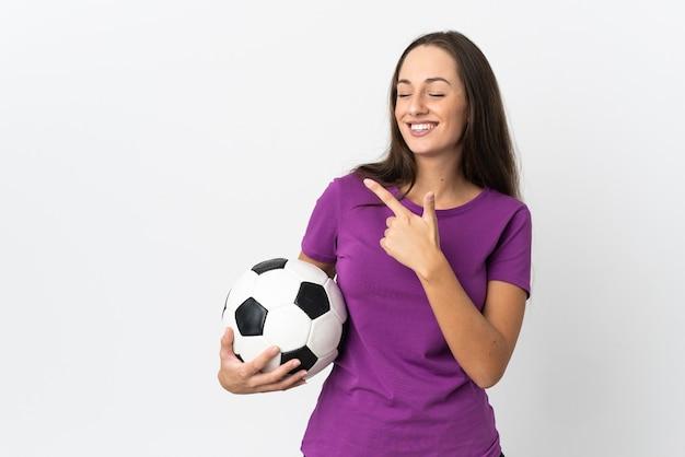 Jovem hispânica sobre fundo branco isolado com bola de futebol e apontando para a lateral