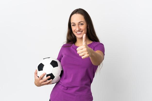 Jovem hispânica sobre fundo branco isolado com bola de futebol e polegar para cima