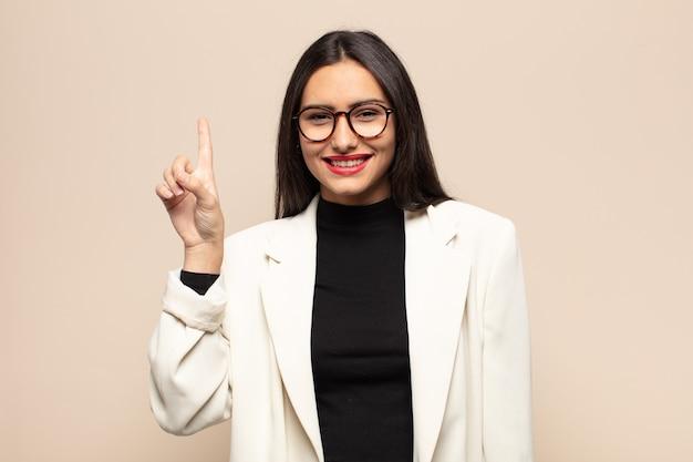Jovem hispânica sorrindo alegre e feliz, apontando para cima com uma das mãos para copiar o espaço