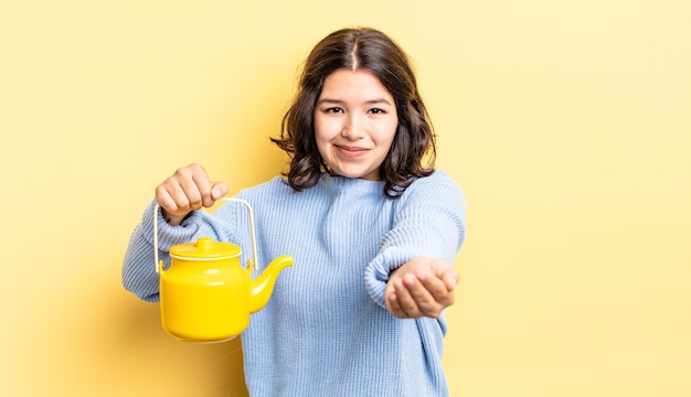 Jovem hispânica sorrindo alegremente com simpáticos e oferecendo e mostrando um conceito. conceito de bule